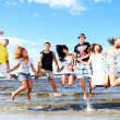 Happy teenagers playing at the sea - Stock Photo