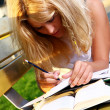 Young and beautiful girl doing home work - Stock Photo