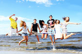 Happy teenagers playing at the sea — Stockfoto