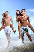 счастливые подростки, играющие в море — Стоковое фото