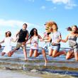 Foto Stock: Happy teenagers playing at the sea