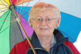 Elderly woman with umbrella — Stockfoto