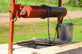 Empty pail, chain and well pulley — Stok fotoğraf