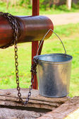 Empty pail, chain and well pulley — Stockfoto