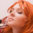 Stock Photo: Ginger womhaving make-up applied