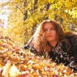 A beautiful ginger-haired woman in fall forest - Stock Photo