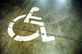 Disabled sign in grunge parking garage — Stock Photo