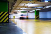 Moving blurred car in parking garage — Stock Photo