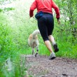 Running in forest with dog - Stock Photo