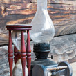 Old dusty oil lamp with a glass bulb and wooden sand clocks. — Foto de Stock