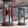 Stock Photo: Two old dusty wooden sand clocks, on wooden background