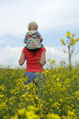 Mother with child on a yellow field — Stock Photo