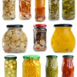 Set of different berries, mushrooms and vegetables conserved in glass jars — Stock Photo #3297678