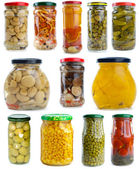 Set of different berries, mushrooms and vegetables conserved in glass jars — Stock Photo