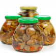 Four glass jars with marinated mushrooms — Stock Photo