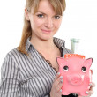 Young woman putting money in piggy bank — Stock Photo