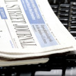 Newspapers on laptop keyboard — Stock Photo