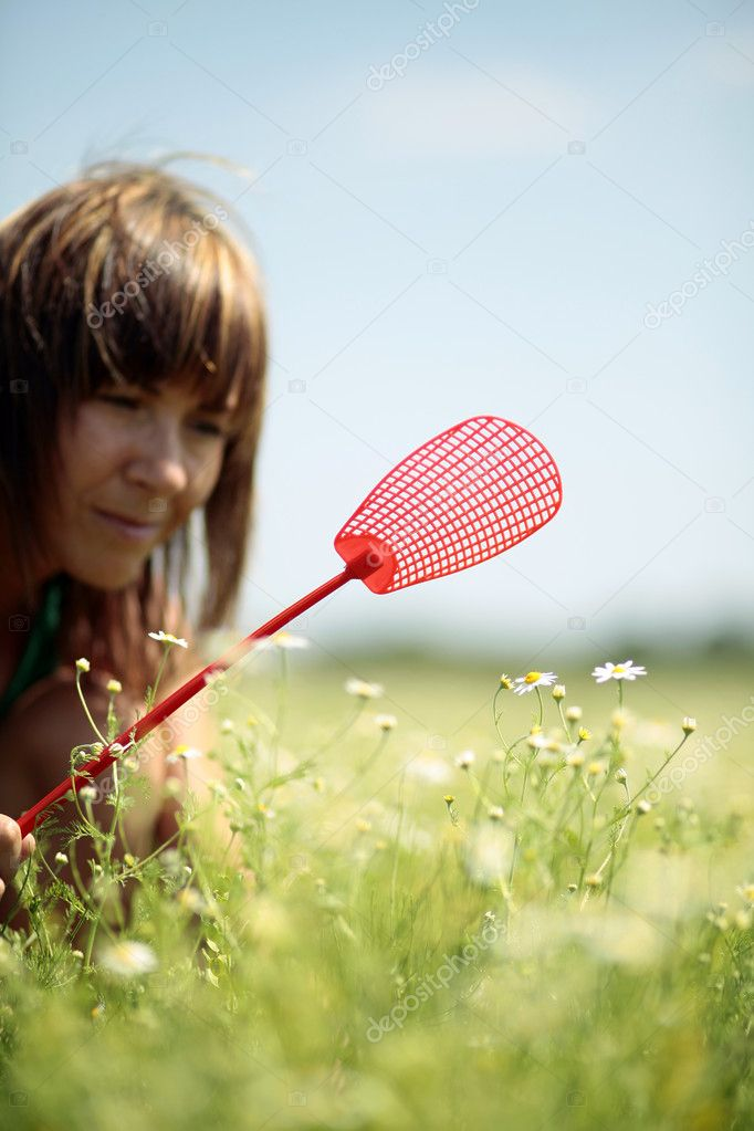 Woman with fly swatter in hand hunting for insect — Stock Photo #3436142