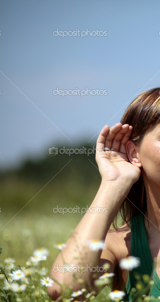 Female hand close to ear agianst the flower meadow — Stock Photo #3436166