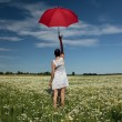 Woman on meadow with umbrella — Stock Photo