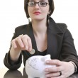 Woman putting coins in piggy bank — Stock Photo #2772535