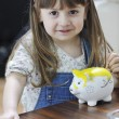 Cute little girl painting piggy bank — Stock Photo