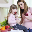 Stock Photo: happy daughter and mom in kitchen