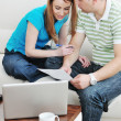 Foto Stock: Young couple working on laptop at home