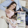 Happy family looking photos at home — Stock Photo