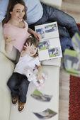 Glückliche familie suchen fotos zu hause — Stockfoto