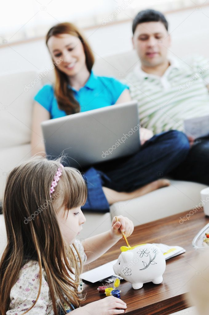 Young happy family at bright and modern living room puting money in piggy bank and working on laptop computer on home finance — Foto de Stock   #2845871