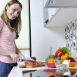 Happy young woman with apple in kitchen — Stock Photo