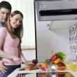 Couple preparing healthy food in kitchen - Stock Photo