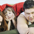 Happy family relaxing in bed - Stock Photo