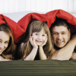 Happy family relaxing in bed — Foto de Stock