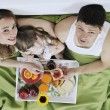 Happy young family eat breakfast in bed — Stock Photo #2856875