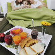 Stock Photo: Happy young family eat breakfast in bed