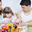 Happy young family eat breakfast in bed — Stock Photo #2856880