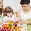 Happy young family eat breakfast in bed — Stock Photo #2856883