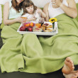 Happy young family eat breakfast in bed — Stock Photo