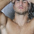 Good looking man under man shower - Stok fotoğraf
