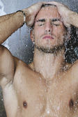 Good looking man under man shower — Stock Photo