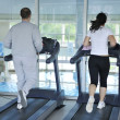 Running on threadmill at fitness club - Stock Photo