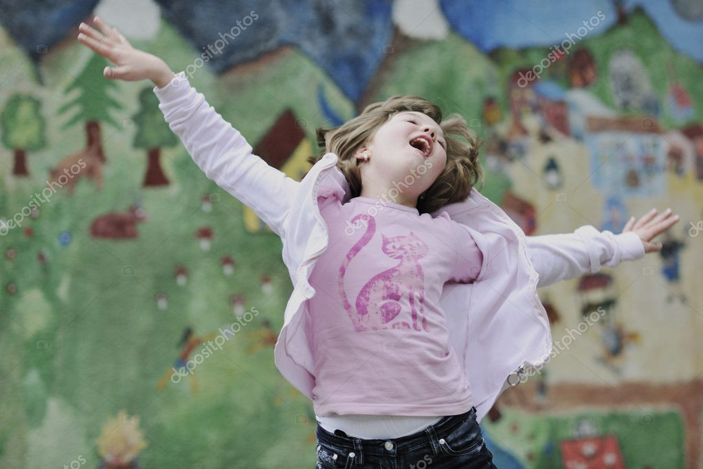 Happy young girl posing and jumping with abstract urban style painting bacground begind — Stock Photo #3193455