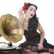 Stock Photo: Pretty girl listening music on old gramophone