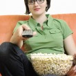 Young woman eat popcorn on orange sofa — Stock Photo
