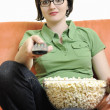 Young woman eat popcorn on orange sofa — Stock Photo #3369626