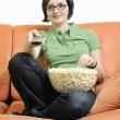 Постер, плакат: Young woman eat popcorn on orange sofa