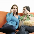 Two young woman eat popcorn on orange sofa — Stock Photo