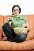 Ung kvinna äta popcorn på orange soffa — Stockfoto